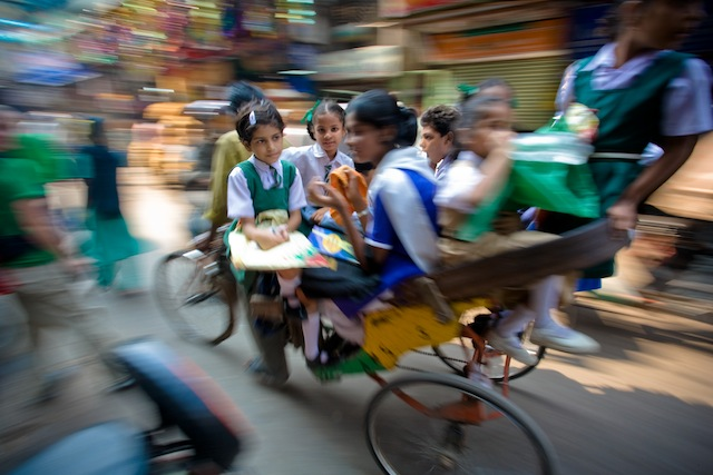 Schoolgirls packed high on a cycle-riskshaw in the crowded streets of Old Delhi, India