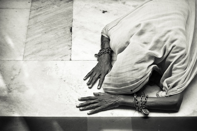 A woman prostrated herself in prayers at the Sufi shrine of Nizamuddin Darga, Delhi, India.