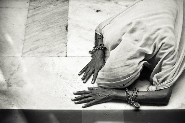 A woman prostrated herself in prayers at the Sufi shrine of Nizamuddin Darga, Delhi, India.