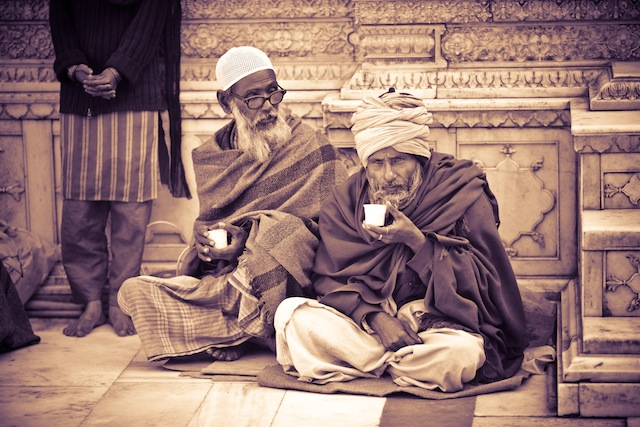 Delhi. Two older men drink chai at Nizzamudin Shrine.