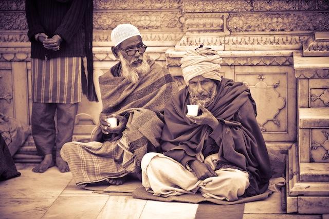 Delhi. Two older men drink chai at Nizzamudin Shrine.